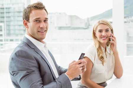 young business people: Young business people using mobile phones in office