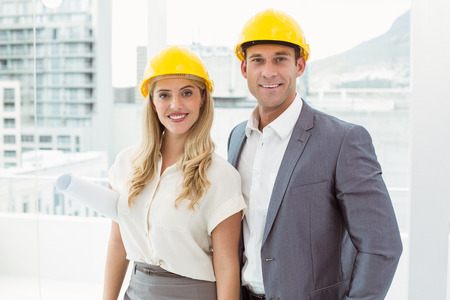hard hats: Portrait of business colleagues wearing hard hats in office Stock Photo