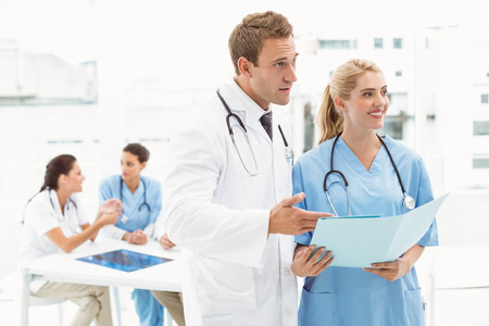 Male doctor and surgeon with reports in medical office photo