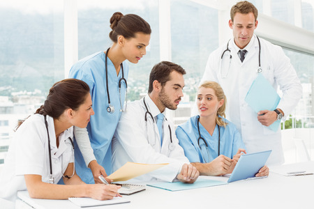 Male and female doctors using digital tablet in medical office photo