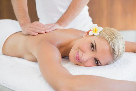 unwind: Close up of an attractive young woman receiving back massage at spa center