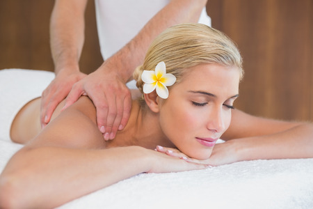 massage table: Side view of an attractive young woman receiving shoulder massage at spa center