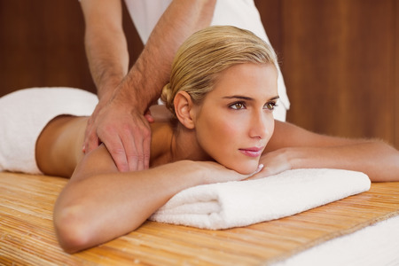 Side view of an attractive young woman receiving shoulder massage at spa center photo