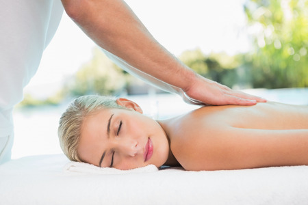 body massage: Side view of an attractive young woman receiving back massage at spa center Stock Photo