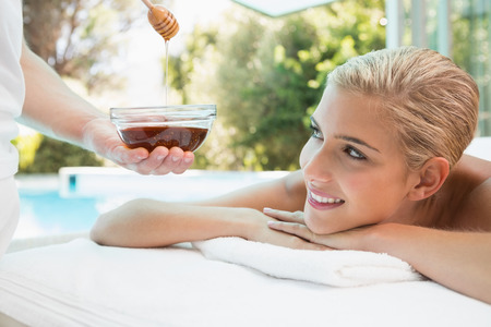 honey blonde: Close-up of an attractive young woman receiving spa treatment with honey Stock Photo