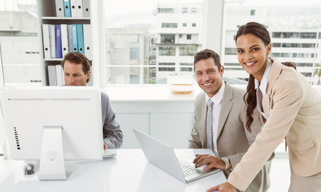 young business people: Three young business people using laptop and computer in office