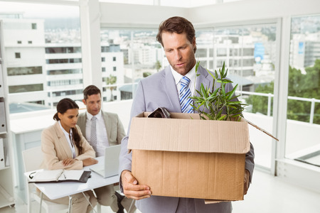 unemployed dismissed: Businessman carrying his belongings in box after being fired Stock Photo