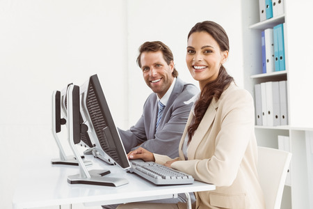 Two young business people using computers in office photo