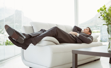 Full length of a young businessman lying on couch in living room
