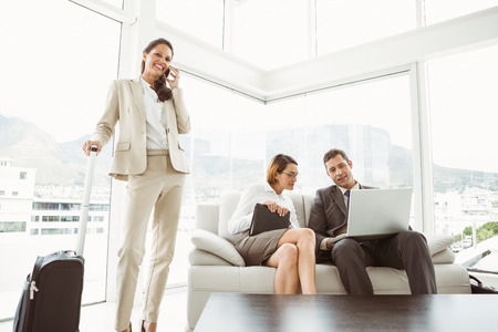 Two young business people using laptop and colleague with luggage in living room photo