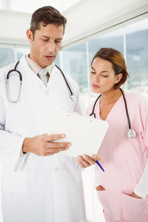 Two concentrated doctors discussing reports at the medical office photo