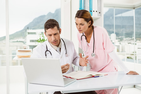 Two concentrated doctors using laptop together at the medical office photo