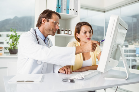 Male doctor showing something on computer screen to patient in medical office photo