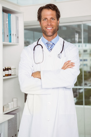 Portrait of confident male doctor standing in medical office photo