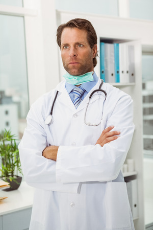 Portrait of serious male doctor with arms crossed in medical office photo