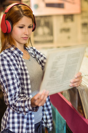 record shop: Girl looking for vinyl while listening to music in the store