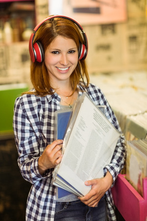 Smiling woman listening music and holding vinyls in the store photo