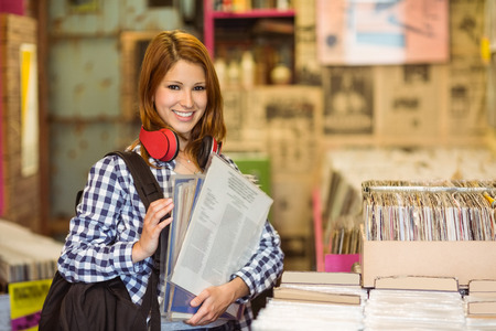 record shop: Smiling girl holding some vinyls in the store