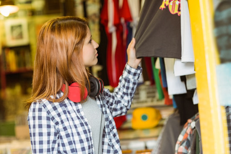 Hipster redhead looking at clothes in the store photo