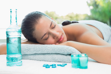 massage table: Beautiful young woman lying on massage table at spa center Stock Photo