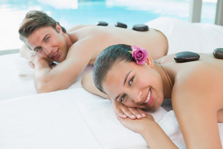 Side view portrait of a young couple enjoying stone massage at health farm photo