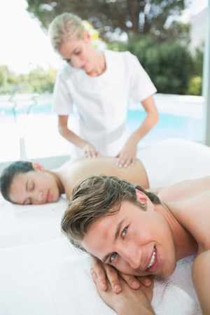 Side view of a young couple enjoying massage at health farm photo
