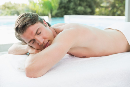 massage table: Handsome young man lying on massage table at spa center Stock Photo