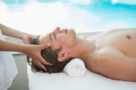 therapy room: Side view of a handsome young man receiving head massage at spa center Stock Photo