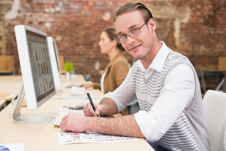 digitizer: Portrait of casual male photo editor using digitizer in the office