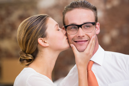 Close up of young woman kissing man in the office photo