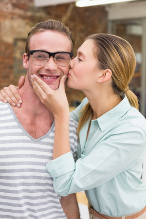 Close up of young woman kissing happy man in the office photo