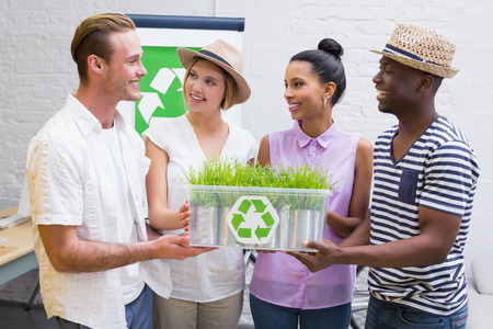 Portrait of creative business team holding plant with recycling symbol in meeting Stock Photo