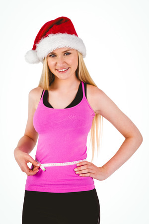 silhouette feminine: Monter festif jeune blonde mesurant sa taille sur fond blanc