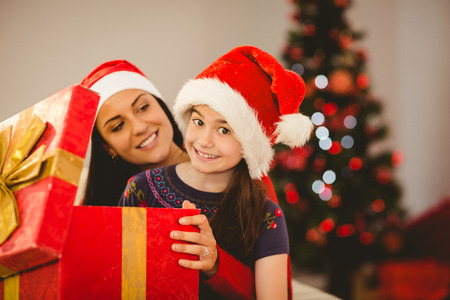 Festive mother and daughter opening a christmas gift at home in the living room photo