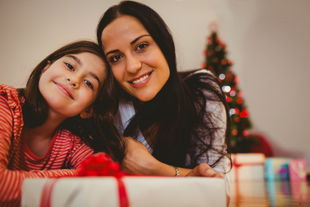 Festive mother and daughter smiling at camera at home in the living room photo