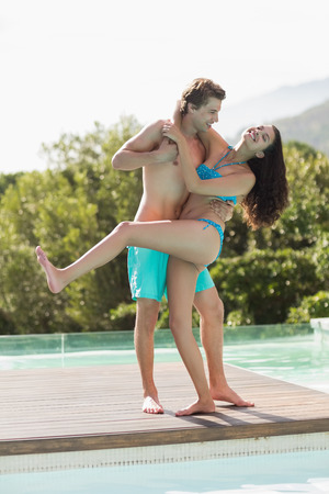 Full length of a romantic young couple by swimming pool on a sunny day photo