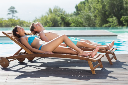 Full length of a young couple resting on sun loungers by swimming pool photo