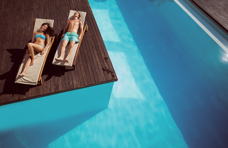 bikini couple: Full length of a young couple resting on sun loungers by swimming pool