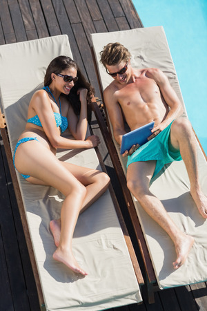 Young couple resting on sun loungers while using digital tablet by swimming pool photo
