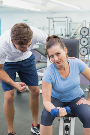 Personal trainer helping client lift dumbbell at the gym photo