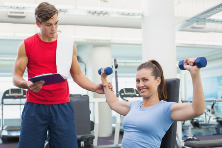 Personal trainer helping client lift dumbbells at the gym photo
