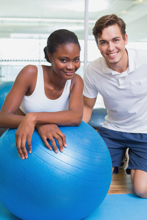 Personal trainer and client smiling at camera with exercise ball at the gym photo