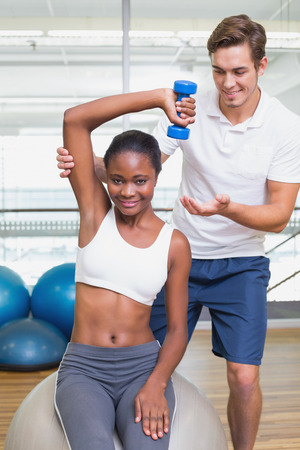 Personal trainer helping client lift dumbbell on exercise ball at the gym photo