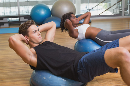 Couple doing sit ups on exercise balls at the gym photo