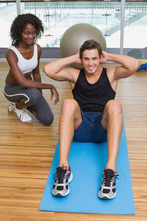 Personal trainer working with client on exercise mat at the gym photo