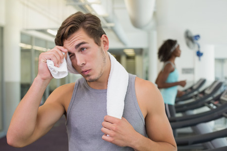 Handsome man wiping his forehead beside treadmills at the gym photo