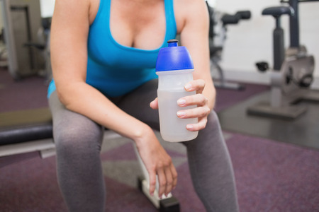 Fit brunette holding sports bottle at the gym photo