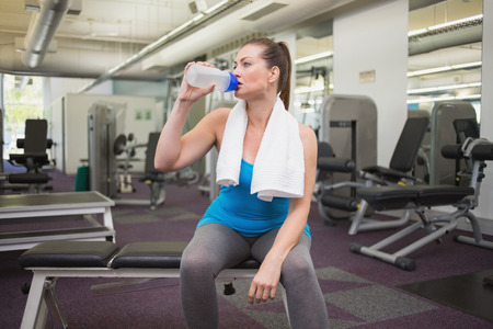 Fit brunette drinking from sports bottle at the gym photo