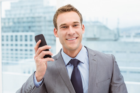 Portrait of smart young businessman using mobile phone in office Stock Photo