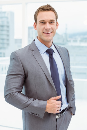 businessman smiling: Portrait of smart young businessman in suit at office Stock Photo